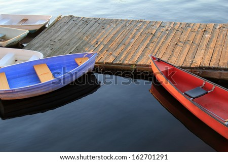 Red,white and blue boats ties securely to old wood dock on calm waters, with sunny skies above.