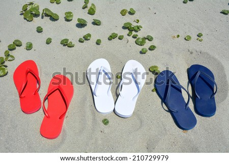 Red white and blue flip flops on the sand.