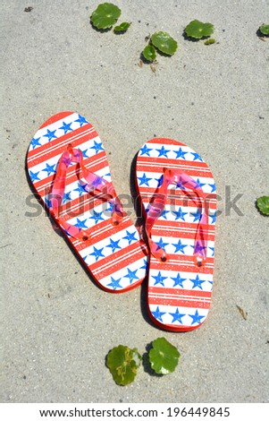 Red white and blue flip flops on the sand. Perfect for cover art - stock photo
