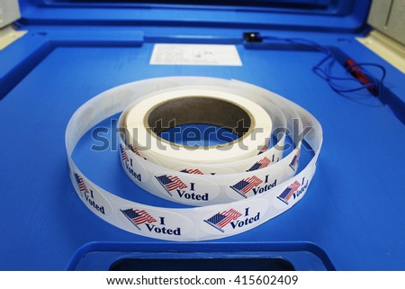 "Red white and blue ""I voted"" stickers with American flag are on a spool of stickers placed on a voting booth platform.  - stock photo"