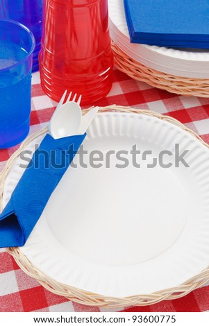 Red, white and blue picnic table setting is ready to celebrate  a festive summer holiday meal. - stock photo