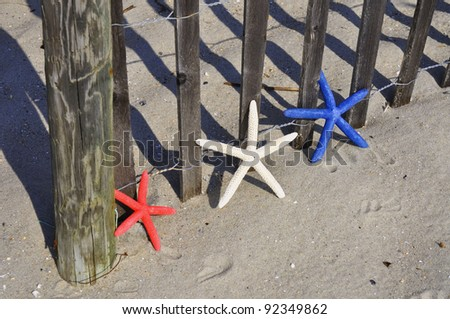 Red, White and Blue Starfish sitting by beach fence. Room for your text - stock photo