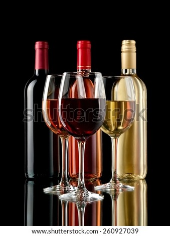Red, white and rose wine glasses and bottles - stock photo