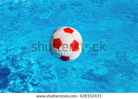 Red white beach ball floating on water in blue swimming pool - stock photo