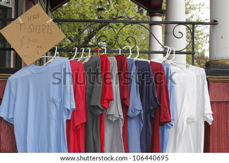 Red, white, blue and gray t-shirts hung up on a porch railing on hangers to sell as part of items at a yard sale. A sign on the left offers the t-shirts for a $1. each. - stock photo