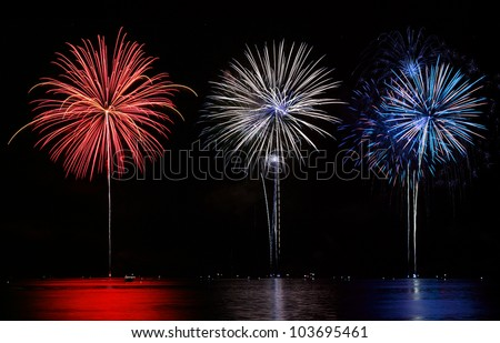 Red, White, & Blue Fireworks reflecting in lake - stock photo