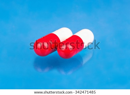 Red white capsules from a headache close up on a blue background - stock photo