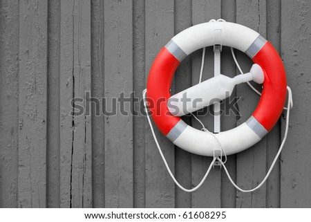 red white lifebuoy on grey wood wall - stock photo