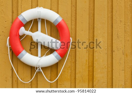 red white lifebuoy on yellow wood wall - stock photo