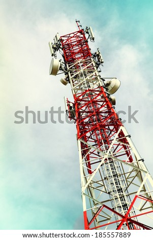 red white metal telecommunication tower on cloudy skies - stock photo