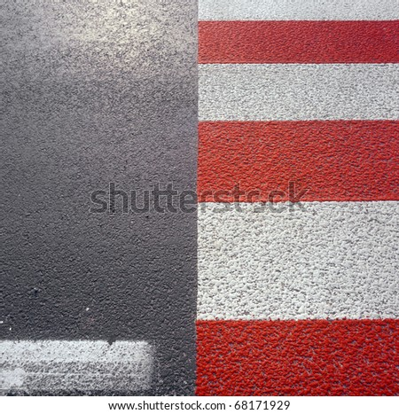 Red - white road marking on a pedestrian crossing. Please see similar photos in my portfolio. - stock photo