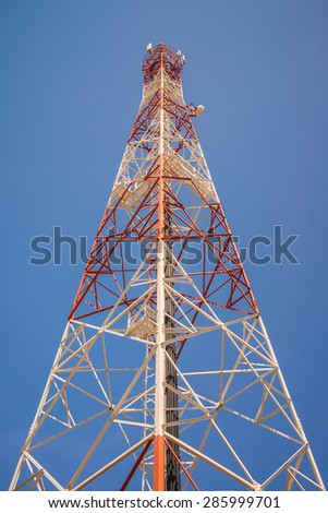 Red white telecommunication tower against blue sky - bottom view - stock photo