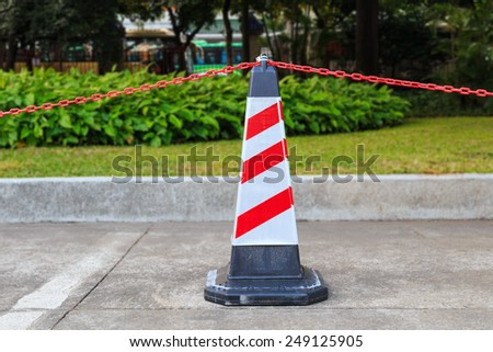 Red-white traffic cone and chain on street for restricted area
