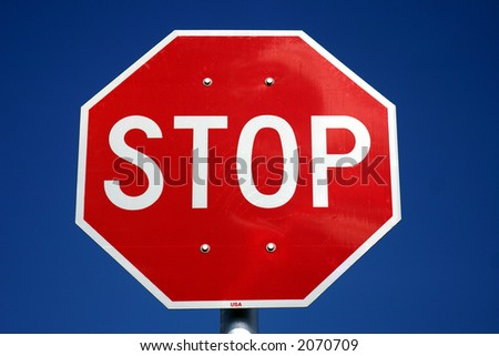 Red & White U.S. style stop sign against a deep blue sky background. - stock photo