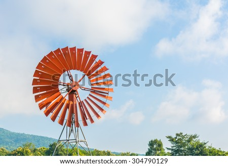 red wind turbine generator with green mountain and blue sky background. - stock photo