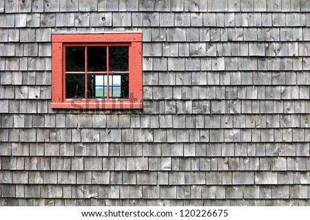 Red window frame in a weathered shingle wall