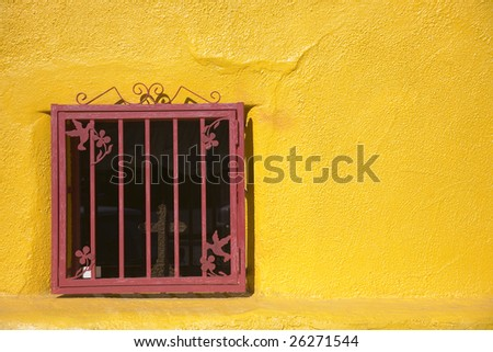 red window in a yellow wall - stock photo