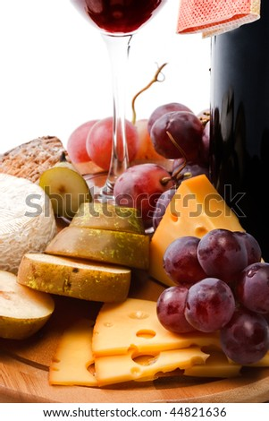 Red wine and assortment of cheese and fruits close-up on white background