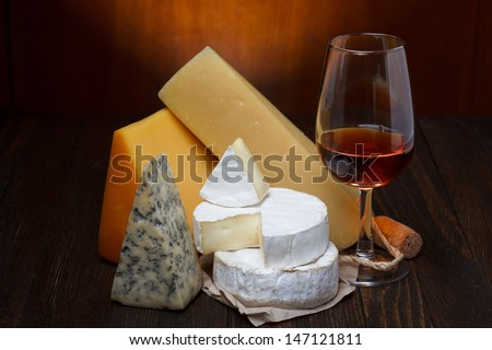 Red wine and cheese assortment on wooden table - stock photo