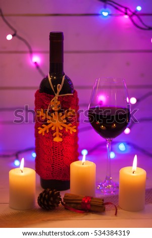 Red wine and Christmas ornaments on wooden table on wooden background. Christmas card