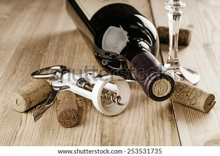 Red wine and corks on wooden background - stock photo