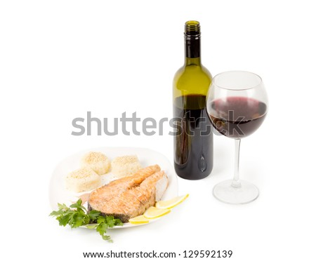 Red wine and delicious fried salmon steak served on a platter - stock photo