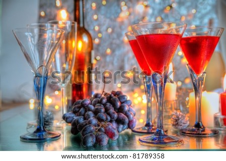 Red wine and grapes,bottles,candle light and lights on background. - stock photo