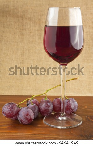 Red wine and grapes on a wooden table