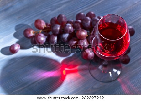 red wine and grapes on blue wooden table