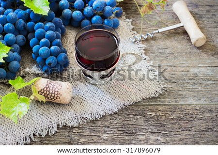red wine and grapes. Wine and grapes in vintage setting with corks on wooden table - stock photo