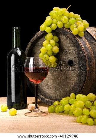 red wine and green grape on a background of old wine barrel