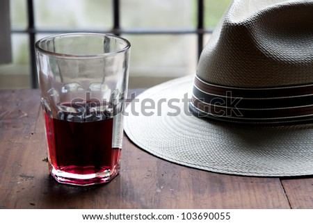 red wine and panama hat over wooden table - stock photo