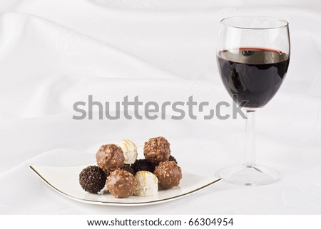 Red wine and plate of chocolate on the table cloth - stock photo