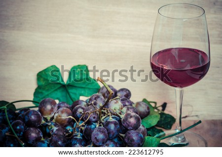 Red wine and red grapes on wood background, the still life with red wine - stock photo