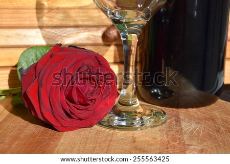 Red wine and red rose. - stock photo