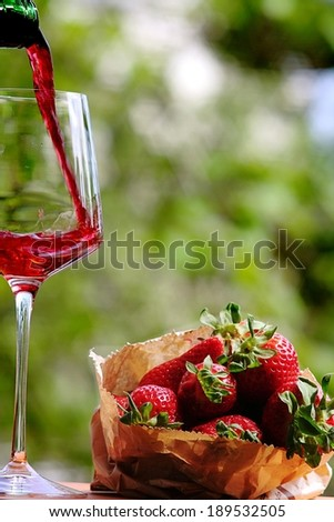 Red wine and strawberries on a summer day - stock photo