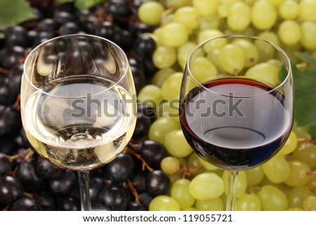 Red wine and white wine in glasses with selective focus - stock photo