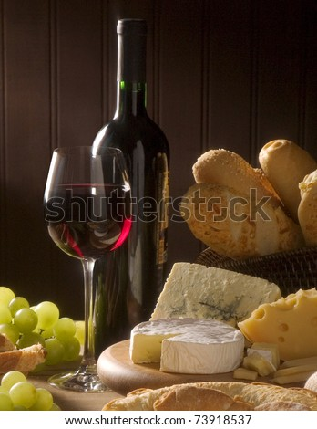 Red wine, assorted cheeses, bread and grapes in a still life setup. - stock photo