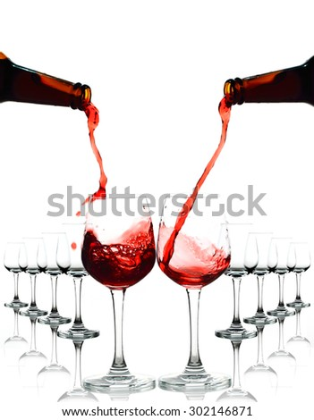 Red wine being in glasses isolated on white background. Splashing stop motion.