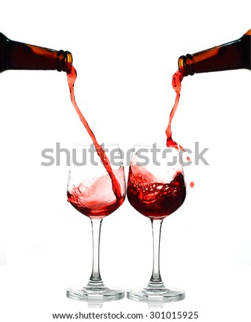 Red wine being in two glasses isolated on white background. Splashing stop motion.