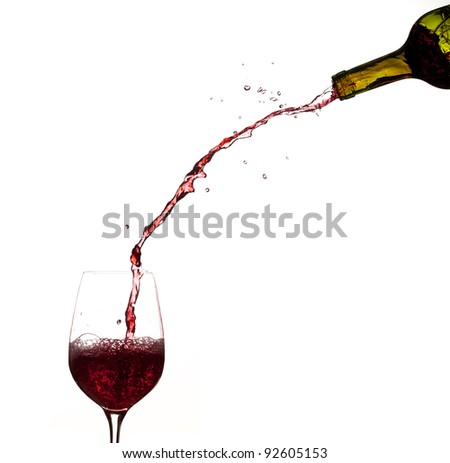 Red wine being poured directly from bottle into a large goblet - stock photo