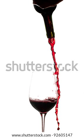 Red wine being poured directly from bottle into a large goblet and missing - stock photo