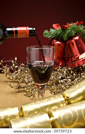 Red wine being poured in a christmas decorated table - stock photo
