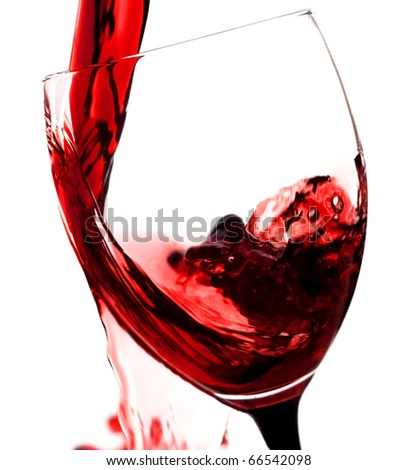 Red wine being poured in a wine glass over white background - stock photo