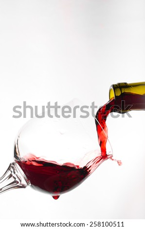 Red wine being poured into a clear wine glass - stock photo