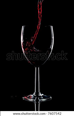 Red wine being poured into a glass and splashing over the side. Low key black background. - stock photo