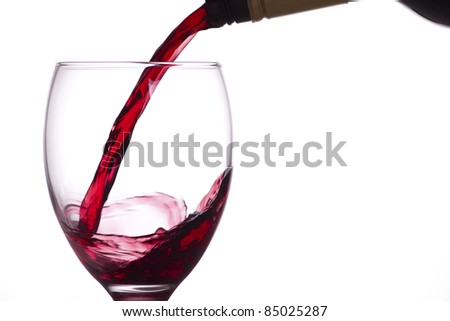 Red wine being poured into a glass from a bottle, white background. - stock photo