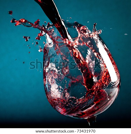 Red wine being poured into a wine glass - stock photo