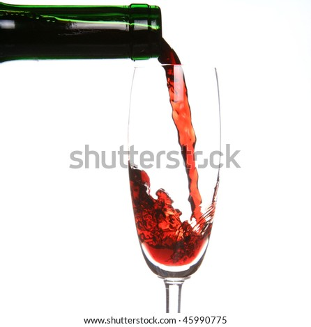 Red wine being poured into a wine glass and a green bottleneck - stock photo