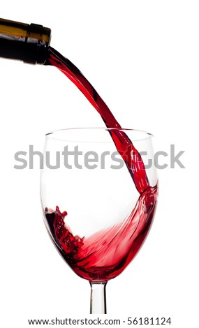 Red wine being poured into clear glass with white isolated background